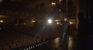 Mike, in hat, coat, scarf, and jeans is standing on a stage, left hand in jacke pocket, right hand stretched out as an actor speaking, with a work lamp in the middle of the picture and the theater seats in the background and to the left