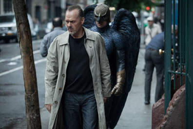 Keaten in black sweatshirt, blue jeans, gray trenchcoat walking down the street (tree on his right, gate on his left) with Birdman in black armor, gold gloves and hood/mask, and large black wings behind him