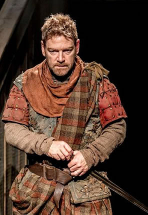 Branagh in orange and brown plad and ancient armor, dagger in hilt.