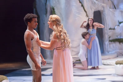 Lysander in white union suit underwear backs away from Hermia wearing a pink gown with her palms on his chest. Int he background, Demetrius, also in white union suit underwear, is on he knees with his hands and face on Helena's waist as she stands in a blue gown with hands up in flustered frustration.