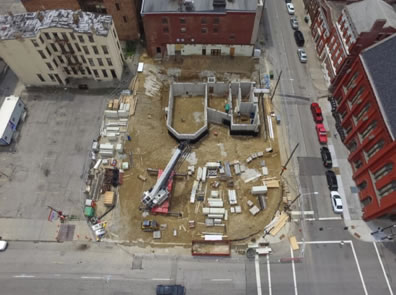 Concrete outlines of the thrust stage and rooms to its right amid a dirt covered block with a crane and other construction gear in an overhead photo