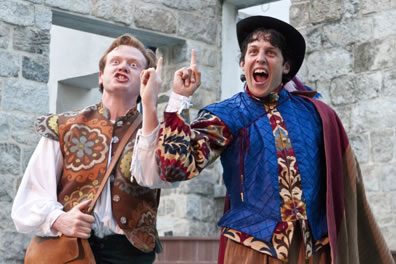 "Tranio in brown flowery vest and blond hair, Lucentia in floral patterend hacket with blue vest, a hat and cape, both with fingers pointed in the air and ""ah-Ha!"" expressions"