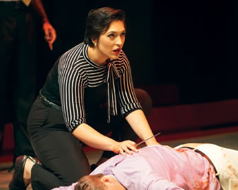 Antonia, in black blouse with black and white striped shoulders and sleeves to elbows and a bow on the collar and black pants kneels next to Caesar's bloody body; she's holding a knife in her righ hand and looking up at someone beyond the body