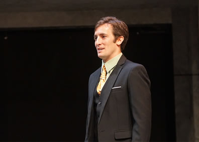 Cassius in three pice suit, dark gray jacket and vest, light green shirt, gold multiknotted tie, sliver of white handkerchief in breast pocket