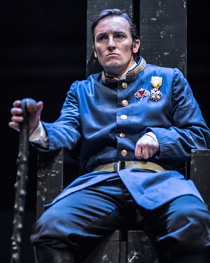 Richard sits on throne, frowning, left hand clinched with crooked arm, right hand on knotty cain, he's wearing a blue early 20th century dress uniform, long dress coat with gold-embroidered uptoruned collar, gold buttons and belt, and two medals on his left breast