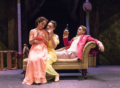 Hermia in a peach gown sits on the lap of Helena in a yellow gown, who sits on the edge of the chaise lounge as Lysander in salmon jacket leans back on the chaise lounge. The women have champagne glasses, Lysander the bottle.
