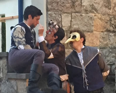 Romeo sits on a step, in blue waistcoat, bue floral patterned shirt, purple pants and black boats as Mercutio, mask perched on his head and in brown checked shirt, tweaks his nose. Benvolio, wearing a  long-nose mask and blue and gray jerkin, stands behind Mercutio, with the stone walls behind them.