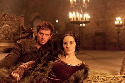 Hotspur in brown leather laies next to Kate in fur cape over borown dress on thrushes in a candlit castle room