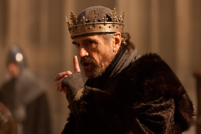 Henry IV, with fur cap and fingerless gloves, simple gold crown over a skull cap, points a finger up as he speaks with a threatening look