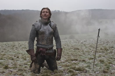 Henry in armor on his knees on the top of a trampled meadow hill with his sword stuck in the ground nearby, and the soldier's gage in his belt