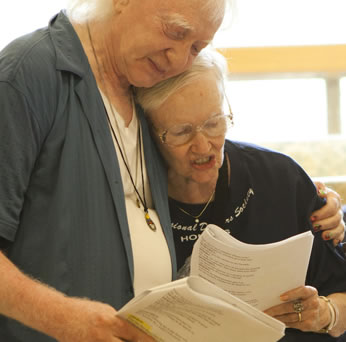 Condos with blue shirt unbuttoned and a white t-shirt underneath, necklaces hanging down around his neck and long white hair hugs Fairchild to his breast  with his left arm around her shoulder, she wearing wireframe glasses and a black t-shirt as she reads a script; both hold scripts in their other hand.