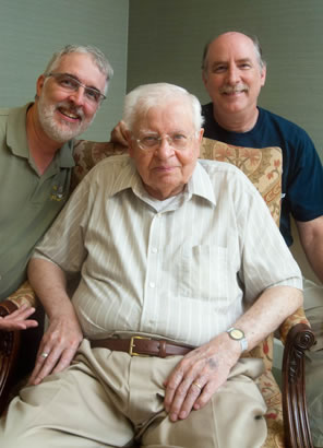 Portrait of my dad sitting in a chair with me on one side and my brother, John, on the other.