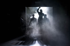 Coming through a large loading dock door with fog rolling in and a bight white spotlight from behind a woman in an overcoat, right fist raised, with other silhouette figures around her