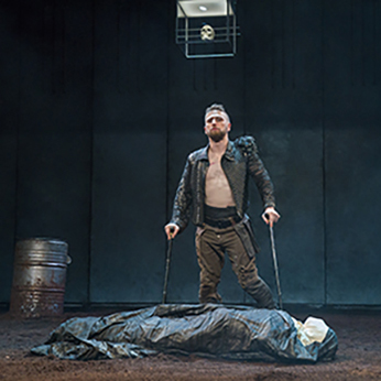Production photo of Richard, in black unbuttoned Renaissance jacket and bround pants, leaning on his two crutches, standing by the shrouded body of Henry VI. The floor is dirt, a barrel is in the background, and a skull is suspended in a glass box hanging from the ceiling.