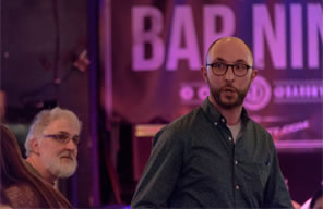 Photo of Jonathan Minton performing Thomas More's speech at Bar Nine, with his father looking on from the side