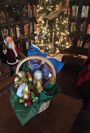 Photo of an Easter basket on a table with an Anna Lee doll Santa standing in the background next to a lit Christmas tree and book shelves.