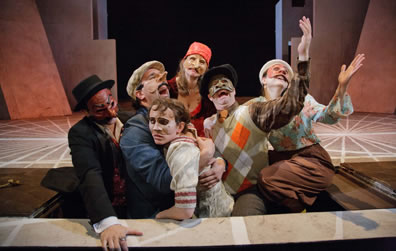 The Faction of Fools cast for Hamlecchino, with arms extended and mouths a-woeing in Opehlia's grave, a trap door on the stage