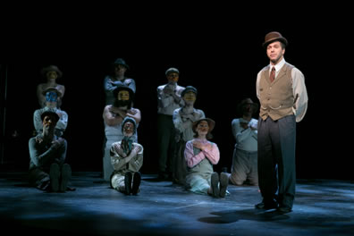 Stage Manager in bowler hat, brown vest and white tie over white shirt and gray pants, behnd him the rest of the ensemble, masked and all with their arms folder over their chests, in three rows: three sitting with legs outstretched in the front, four kneeling, and three standing.
