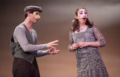 George wearing brown dog cap, gray sweater vest, purple longsleeve under shirt and brown pants with hands motioning as he explains something, Emily in simple gray and purple print dress, a blue bow in her hair, looking out at the audience, her fingernails tentatively touching at her waist.