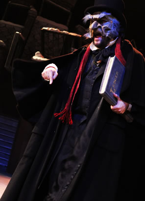 Scrooge in Victorian overcoat and eagle-like mask, carrying a ledger and angrily pointing his finger down.