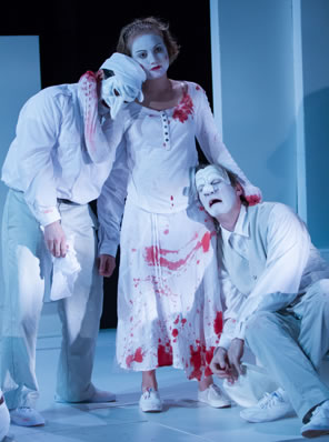 All in white, Lavinia in blood-stained dress and bloody stumps stands in the center with one arm hugging the neck of Titus and the other on the shoulder of Marcus as they grieve over her mutilation. Titus is wearing a white commedia mask and a soldiers cap, Marcus is in white face