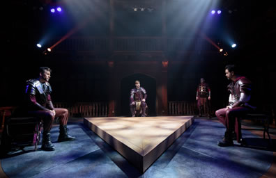 Lepedus, Octavius, and Antony sit on either side of a triangle platform in the middle of the floor, all dressed in leather armor.