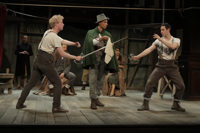 Hamlet and Laertes in farm pants and suspenders poise to duel with swords as Osric, in green cloak and hat, holds a handkerchief over the crossed swords