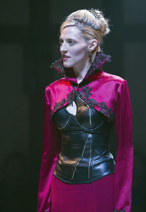 Elizabeth in red dress with black trim on high collar and black leather corset