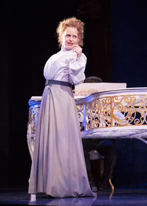 Tonya Beckman in simple Victorian-era white blouse and gray floor-length skirt stands next to a gold-etched white piano