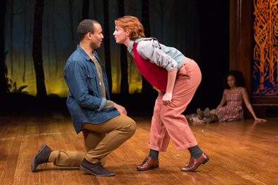 Orlando in blue denim shirt jacket, olive green long-sleeve tee, brown slacks and brown shoes is on one knee as Rosalind in her Ganymede disguse of red vest, denim shirt, pink slacks and brown patent leather shoes talks in his face. Celia, in a plaid country dress, sits on the stage in the background.
