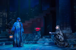 Caesar in a long overcoat and a beard holds the lanter, Brutus, also in overcoat, kneels and reaches toward the ghost. The glowing bowl is in the center of the picture, and behind Caesar barely visible in the shadow-patterend light is the Soothsayer sitting on the steps rising at the back of the stage.