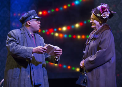 Hoke in overcoat and scarf and chauffeur's cap holds a small package in his hand as he talks with Daisy in simple overcoat with fur collar and hat featuring red and white flowers. Christmas lights in the background
