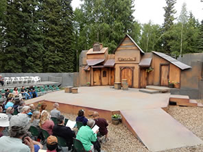 Photograph of the outdoor Fairbanks Shakespeare Theatre stage, with the wood facade Merry Wives set, ramps into the audience in chairs on the ground and platforms. Trees in the background