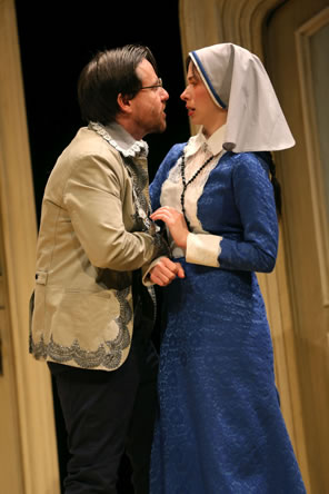 Angelo in a brocaded jacket and lace color grabs hold of Isabella in floor-length blue dress with white bib front and a veil over her head.