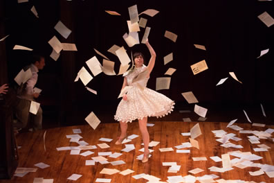 Sylvia in a thigh-high, billowing white dress with papers falling all around her.
