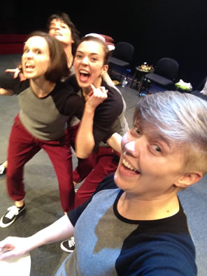 A selfie with a smiling Davidson in front and crowded behind the three actresses playing Weird Sisters wearing red sweat pants and two-tone blue t-shirts