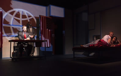 Brutus sits at a table, Cassius stands behnd his left shoulder, ehind oth a screen shows a line-graphic of the globe, an American flag is daped on the open door next to Cassius, and spotlighted to the right of the stage is a fully-clothed Antony lying in bed with Cleopatra, who is under red satin sheets