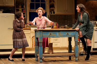 Lenny stands beside kitchen prep table in old fashioned brown and blue print dress, knock-kneed and hand to mouth; Babe behind the table, in curlers and pink blouse, her hands outspread as she talks; Meg sitting on stool at other end of table in low-cut green dress with black boots, hands on table smiling.