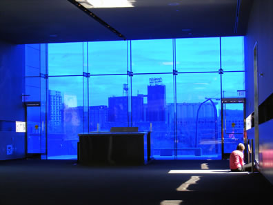 A large plate glass window looking out onto a skyline, lights coming through other windos, one illuminating a woman sitting on the floor writing in a book.
