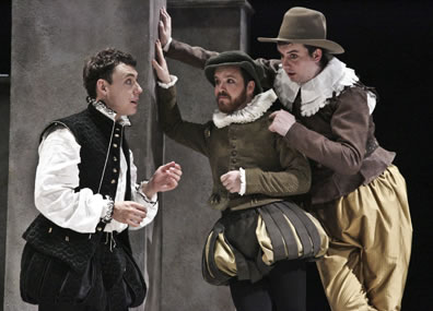 Hamlet in bulging black Elizabethan-style breeches, black vest and high collar white shirt to the left talks with Rosencrantz in green and gold breeches and jacket with white ruff collar dog cap and Guildenstern in gold pants brown jacket and lace collar with country brimmed hat, both leaning against a wall