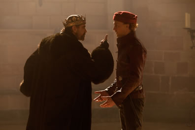 Henry in long fur robe and crown sticks a finger up at the face of Hal in red short jacket and red cap, his hand out in ront of him. Stone wall in the background.