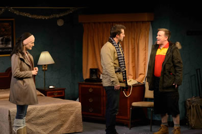 In the motel room, cast in winter jackets, Terrence (in orange and yellow uniform shirt) talks with Josh to one side while Ayelet watches to the side; you can see silver tinsel strewn over the bed.