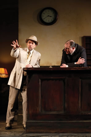 Erie in white sport jacket and fedora gestures with his hand as he talks, leaning on the hotel counter behind which is tne night clerk, hunged over, arms crossed, listening.