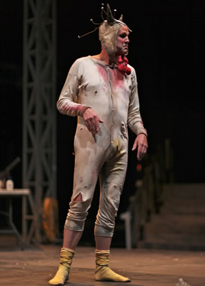 Malvolio in tattered long johns, skull cap with horns, turkey wattle around his chin, and yellow stockings on his feet