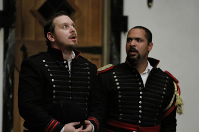 Iago and Othello on their knees, both in uniform, Othello's with shoulder bourds and gold and red braids, with his collar undone as he looks at Iago with concern