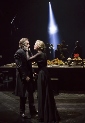 Lady Macbeth has her hands on Macbeth's cheeks, in the background is the banquet table and lords are milling in the darkness with a single shaft of light shining down