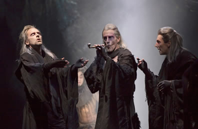 The three weird sisters in long hair and lose black robes and fingerless gloves, the one in the center smoking a pipe, the one on the left enjoying the affects of having just toked on the pipe.