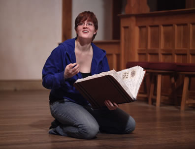 Faustus kneels on the floor with a large book of spells in her hand as she talks out toward the audience