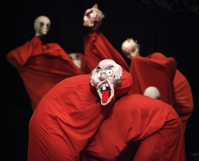 Characters in single red sheets and grotesque masks, the one in front with his mouth wide open and a large red tongue sticking out