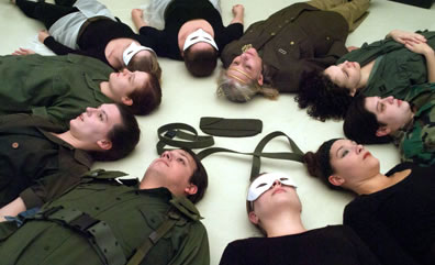 The cast lies on their backs on the ground in a circle, heads facing inward, the witches in white masks, olive green belt and a sky cap in the middle of the circle